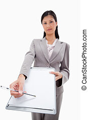 Clipboard and pen being handed over by businesswoman