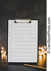 clipboard with blank list with cases to tick off on wooden desk with string lights bokeh in the background