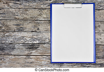 Clipboard with blank white paper on a wooden table