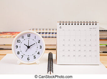 Clock and April 2017 calendar on table
