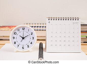 Clock and April 2017 calendar on table