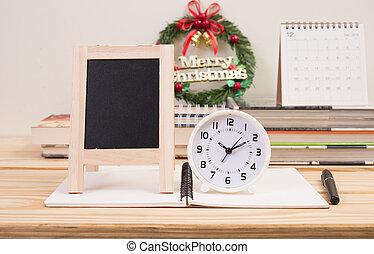 Clock and blackboard Christmas wreath on table
