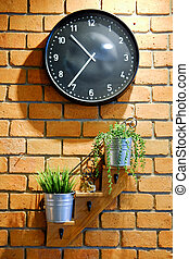 Clock and flower pots on red brick wall