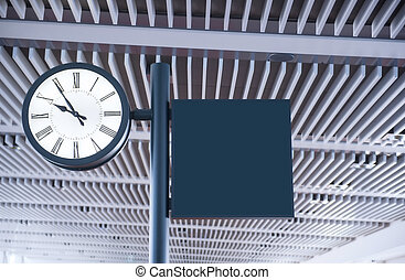 Clock at an international airport and sign