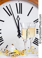 About to strike midnight on New Year Eve with champagne glasses and streamers in front of a large clock face.