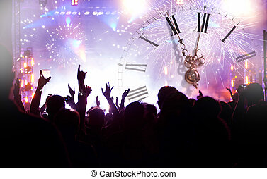 Clock close to midnight, fireworks and crowd waiting for New...