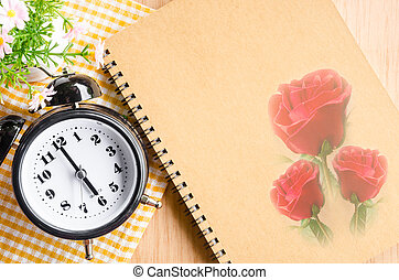 Clock diary brown color with red rose on wooden
