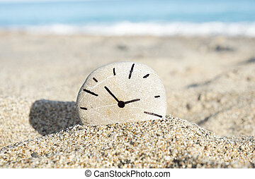 clock drawn on a stone, on the sand of a beach