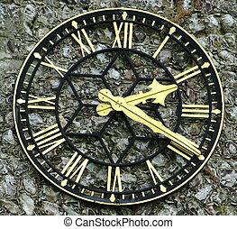 Clock face - Close up of clock face on flint wall.