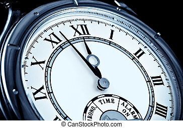 Analog wrist watch closeup at five to twelve