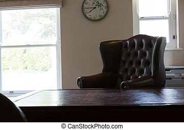 Clock hanging on wall with arm chair in living room