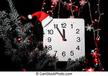 Clock in branches of New Year's fir on black background. Second hand moves in circle of mechanical clock and show Twelve o'clock at  Midnight