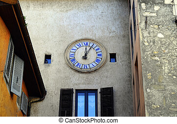 clock in the old town of annecy - clock on medieval stone...