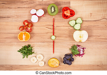 Clock made of fruits and vegetables showing time 6 pm, time for healthy dinner concept