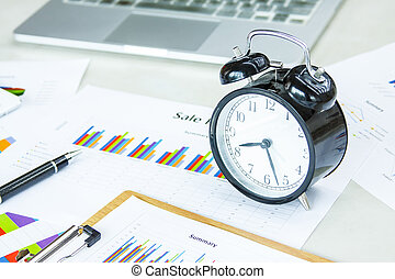 Clock, notebook and pen on a market report