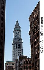 Clock on Public House Through Buildings