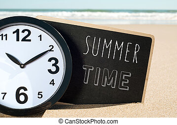 clock on the beach and text summer time