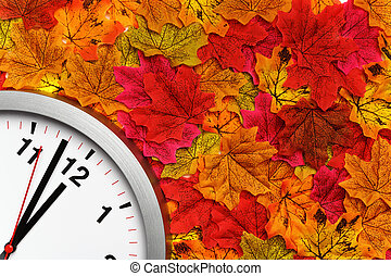 Clock on the colorful autumn maple leaves. Change of season time