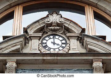 Clock on the facade of an old house.