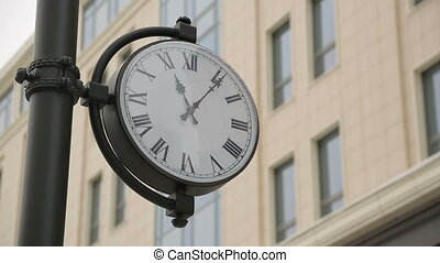 Clock on the pillar - building in background. Pan