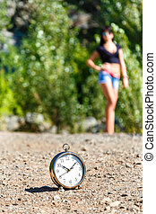 clock on the stone road and blurred girl at sunny day.