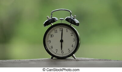 Clock ringing against green background