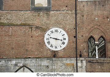 the clock of the palace Santa Maria Della Scala in Siena, Italy