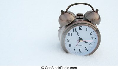 Clock stands in winter on white snow in evening, time lapse
