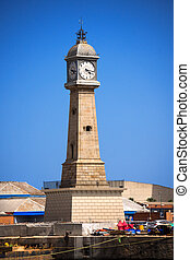 Stone tower with clock (Torre del Rellotge) one of the city most iconic buildings - built in 1772 in Port Vell, Barcelona Spain