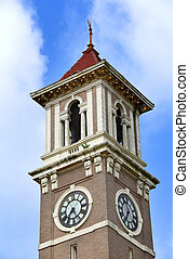 Clock tower on the Monroe County Courthouse in Clarendon, Arkansas, shows 7:20.  Tower is tan brick with white accents and is caped by a red filial.