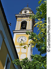 Yellow church clock tower against blue sky, Locate Di Triulzi, Milan, Lombardy, Italy