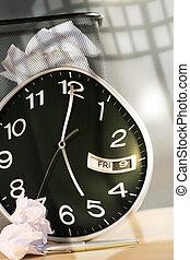 Clock, wast paper basket on desk