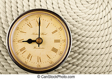 Clock with Roman numerals on cord background. 9