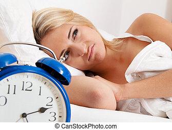 clock with sleep at night. woman can not sleep.
