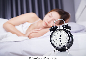 clock with woman sleeping on bed
