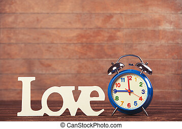 Clock with word love on wooden table.