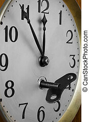 Old clock face with key inserted in the keyhole