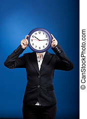 Beautiful young business woman olding a clock over a blue background