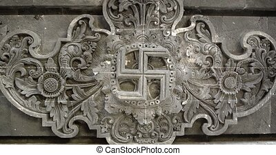 Clockwise swastika, an ancient religious symbol of prosperity, carved prominently into a relief sculpture at a Balinese temple. 4k video