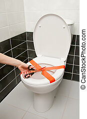 Scissors cutting the adhesive tape on the toilet