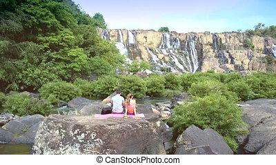 close backside guy girl sit on rock watch waterfall
