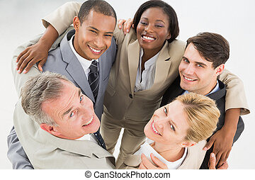 Close business team embracing in a circle smiling up at camera