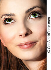 Close face of cute young woman looking up