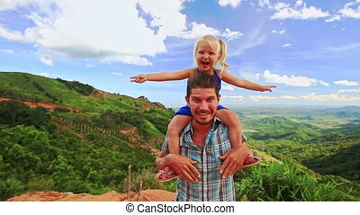 Close Father Holds Blond Girl on Shoulders Hands Aside by Valley
