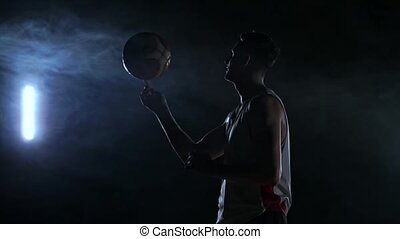 Close footage of basketball player spinning ball on his finger, dark misty room with floodlight.