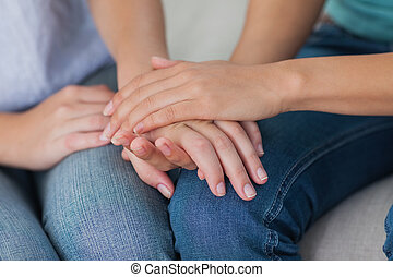 Close friends touching hands at home on the couh