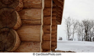 Close image of the log house tenon trees covered in snow