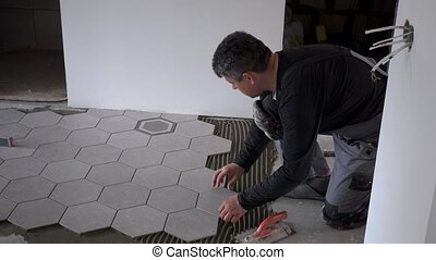 Close look at construction worker laying down hexagon tiles...