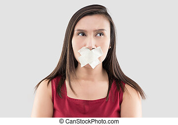 Asian women in red dresses use masking tape to close the mouth because they do not want to comment on a gray background, Thai female in with adhesive tape over his mouth, Stop talking