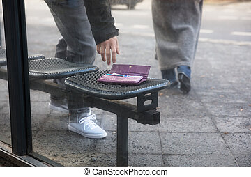 Man Picking Up A Lost Purse On Bench
